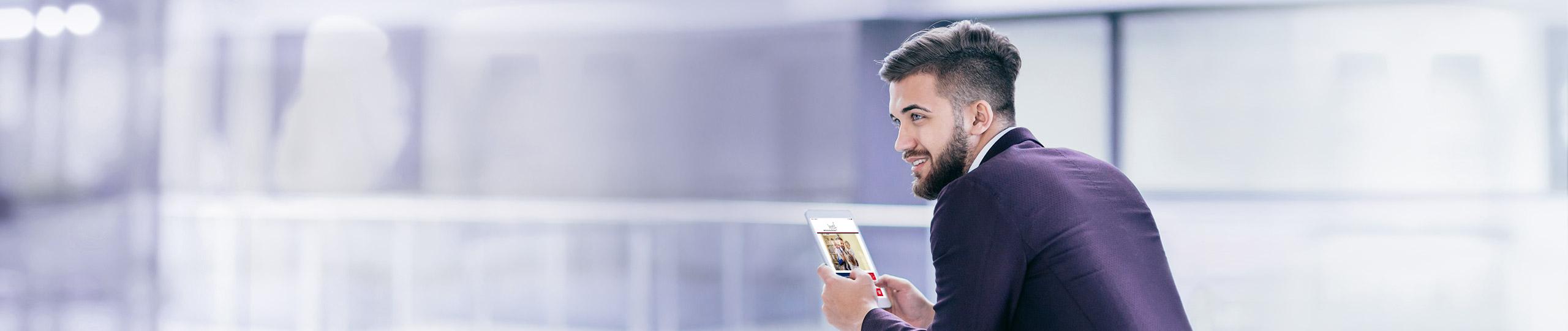 Mann in Anzug und mit Smartphone in der Hand