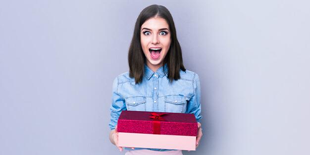 Junge Frau hält Geschenk und lacht